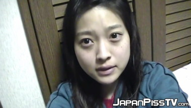 Adorable Japanese chick sits on the toilet and pees in a cup
